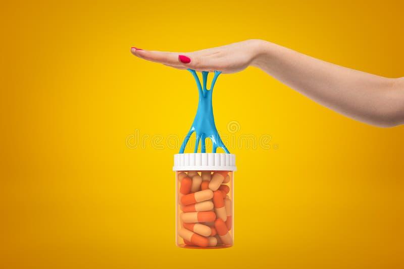 Seitenerntenahaufnahme der Hand der Frau Plastikglas Pillen halten, das an ihrer Palme mit blauem klebrigem Schlamm festgehalten  lizenzfreie stockfotos