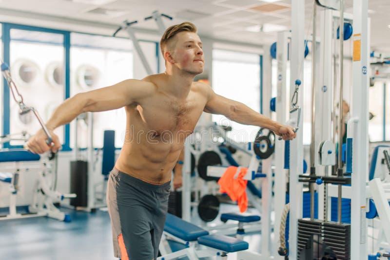 Seitenfoto des Manntrainings auf Eignung-Station Kerl hat perfekten Körper Er ausarbeitend, um zerrissen zu werden, entwickelt St stockbild