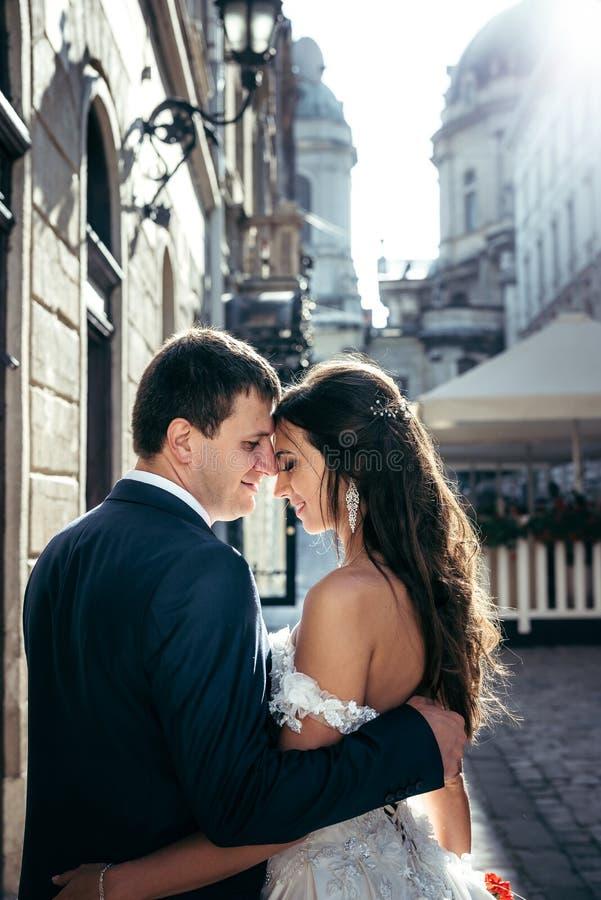 Seitenporträt der entzückenden lächelnden Jungvermählten, die weich Kopf-an-Kopf- im Freien umarmen und stehen lizenzfreie stockfotografie