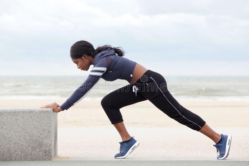 Seitenporträt der geeigneten jungen Afroamerikanerfrau, die Muskeln am Strand ausdehnt lizenzfreie stockbilder