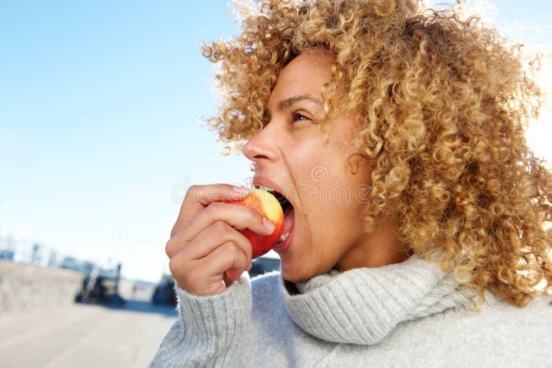 Seitenporträt der gesunden jungen Afroamerikanerfrau, die Apfel isst stockfoto