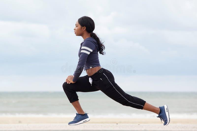 Seitenporträt der gesunden jungen Afroamerikanerfrau, die Muskeln am Strand ausdehnt stockbild