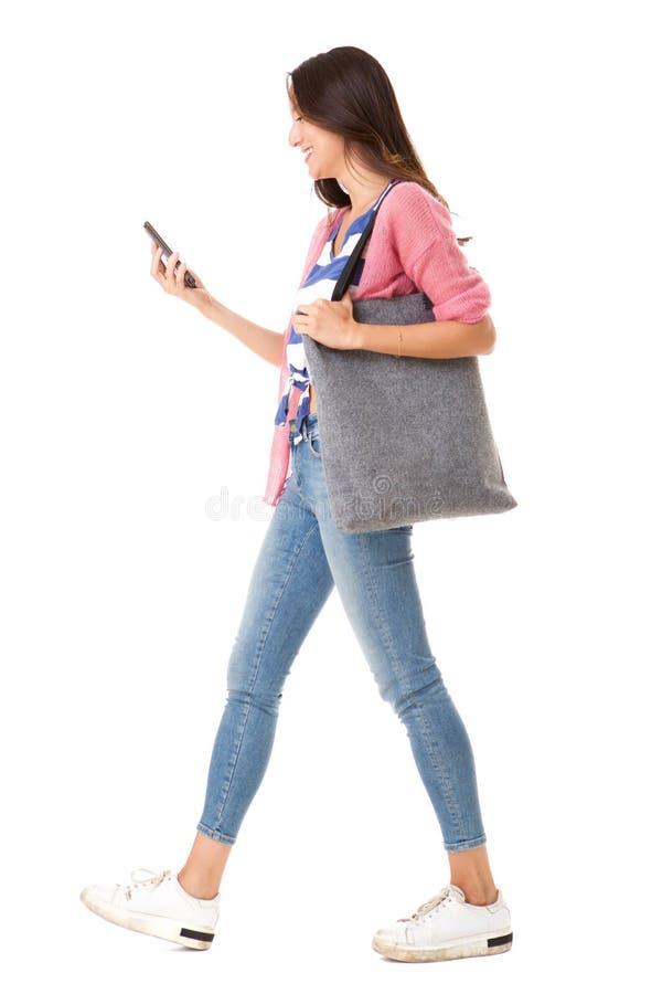 Seitenporträt der modernen jungen asiatischen Frau, die mit Geldbeutel und Handy gegen lokalisierten weißen Hintergrund geht lizenzfreies stockbild