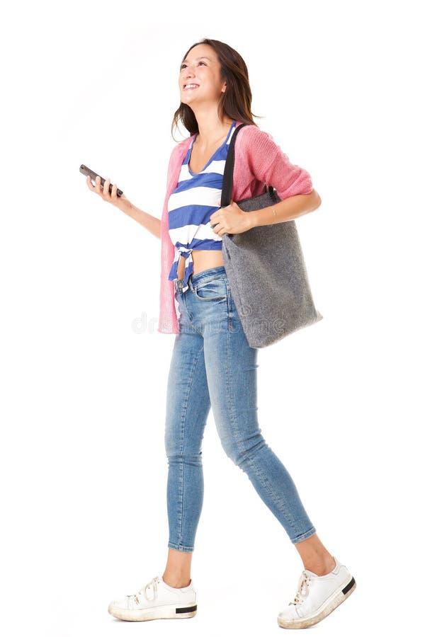 Seitenporträt der modernen jungen asiatischen Frau, die mit Handtasche und Handy gegen lokalisierten weißen Hintergrund geht lizenzfreie stockfotografie