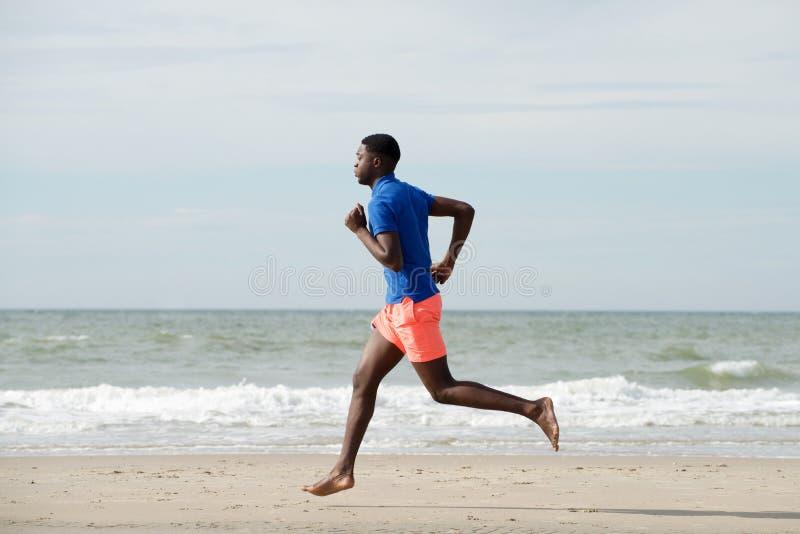 Seitenporträt des gesunden Afroamerikanermannes, der am Strand läuft stockbilder