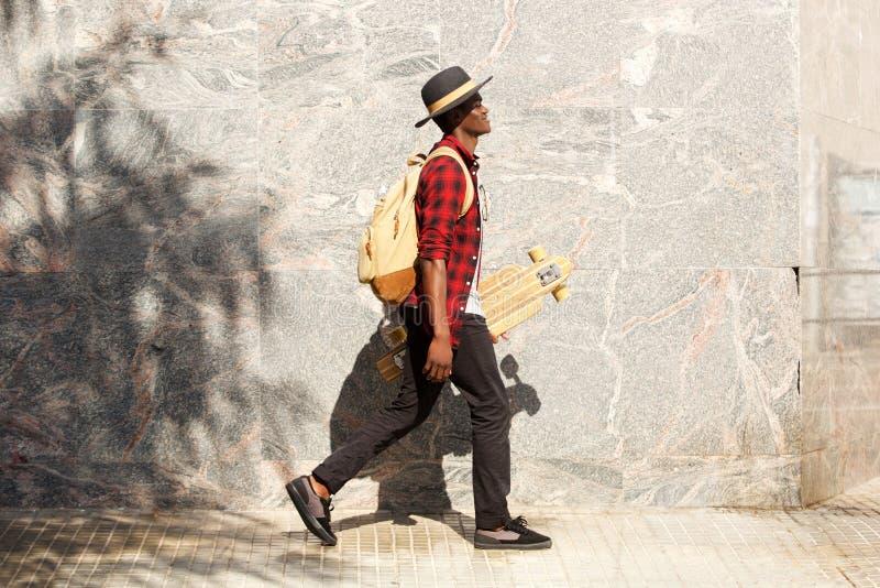 Seitenporträt des jungen Afroamerikanermannes, der draußen mit Skateboard geht stockbilder