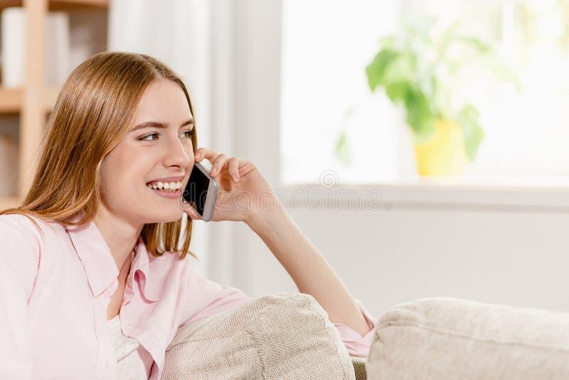 Seitenporträt des Mädchens sitzend auf Sofa, lächelnd und am Telefon sprechend stockfotografie