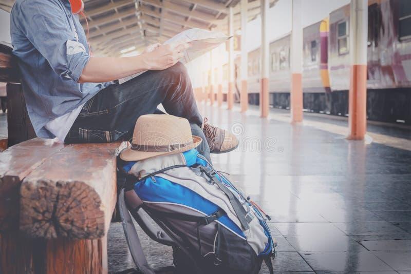 Seitenporträt eines Reisenden des jungen Mannes, der mit Karte sitzt, wählen w stockfoto