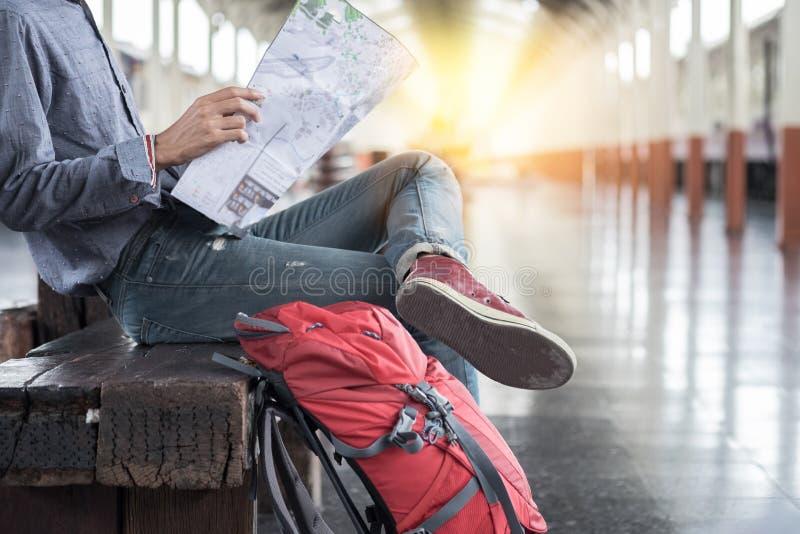 Seitenporträt eines Reisenden des jungen Mannes, der mit Karte sitzt, wählen wh lizenzfreies stockfoto