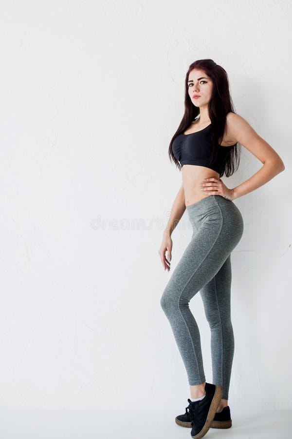 Seitenporträt in voller Länge der jungen athletischen Frau in den schwarzen kurzen Spitzen- und grauen Gamaschen, die am weißen H lizenzfreie stockfotos