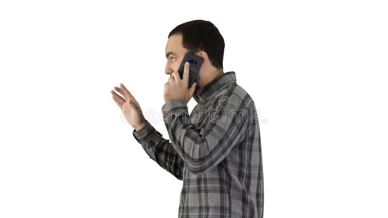 Seitenportr?t eines gl?cklichen Studenten, der am Handy auf wei?em Hintergrund geht und spricht lizenzfreie stockfotos