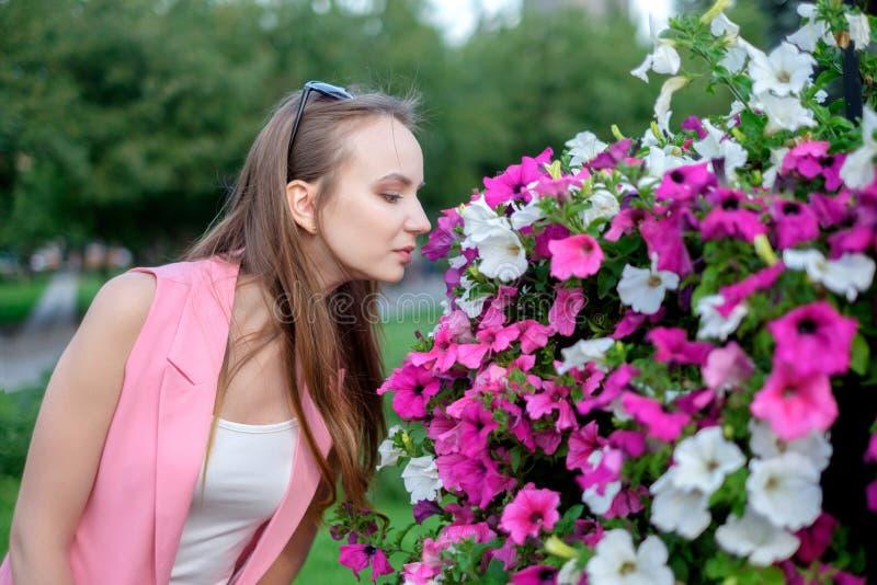 Seitenprofil von riechenden Blüten der jungen Frau stockfotografie