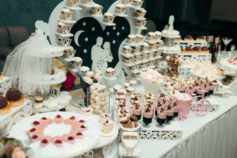 Seitenschuss-Hochzeitstafel-Nachtisch-Stangen-Rosa-Weiß hört Paar-Liebes-Bonbon-Süßigkeiten Jelly Macarons Cupcakes stockfotos