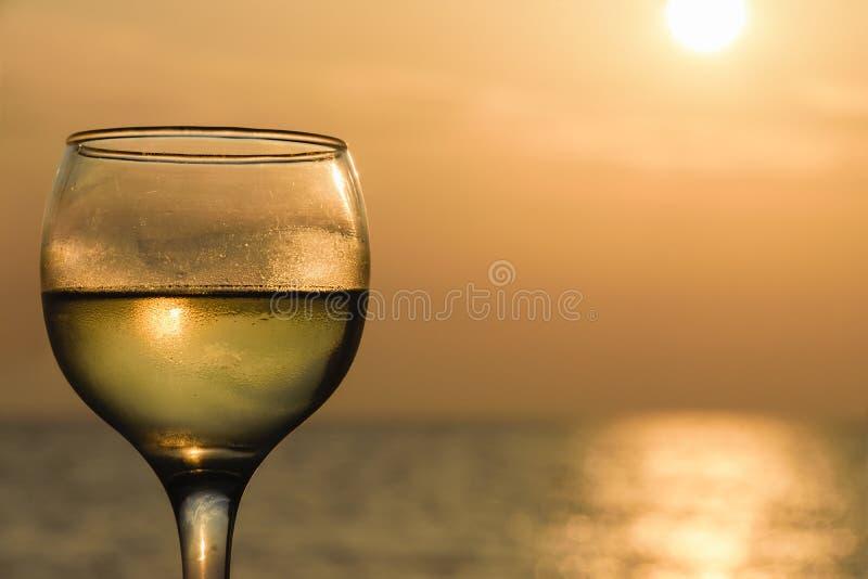 Seitenwinkelsicht des Glases gefüllt mit Weißwein gegen Meer während des Sonnenuntergangs stockfotos
