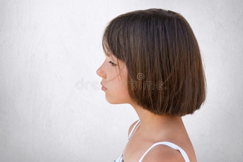 Seitlich Porträt des entzückenden sommersprossigen Mädchens, das Abstand beim Haben des träumerischen Ausdrucks über weißer Beton lizenzfreie stockfotografie