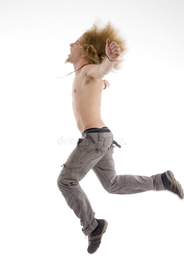 Seitliche Haltung des Mannes springend in einer Luft stockbild