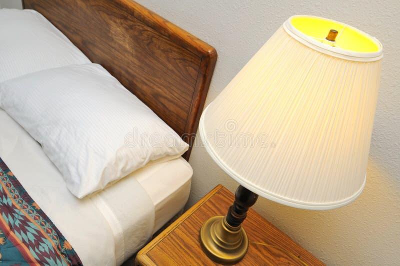 Seitliche Tabellenlampe mit Bett lizenzfreies stockfoto