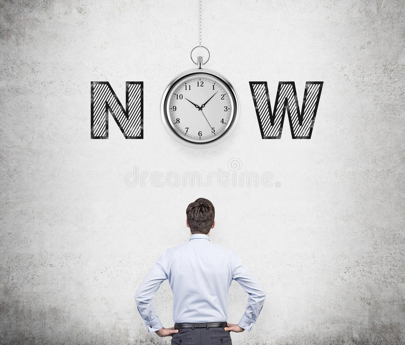 Seize the moment. A young man with hands on hips thinking about present opportunities and time. A pocket watch and the word 'now' over his head. Concrete royalty free stock image
