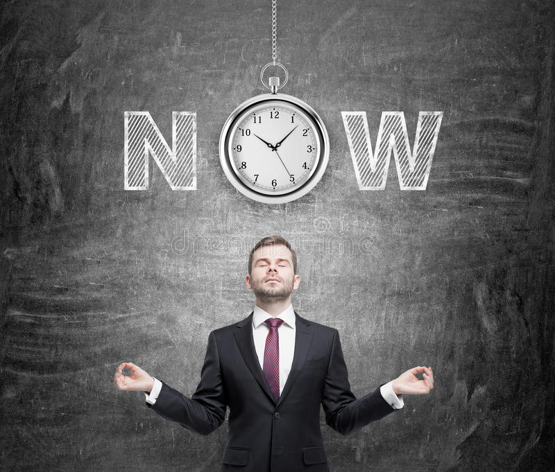 Seize the moment. A young man standing in the posture of meditation thinking about present opportunities and time. A pocket watch and the word 'now' over his stock image