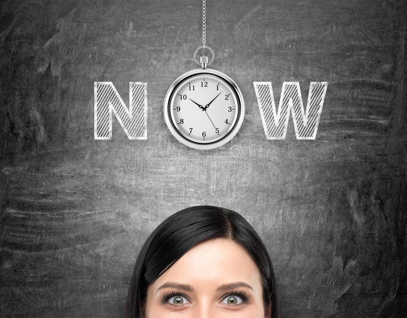 Seize the moment. A young woman looking in front of her and tthinking about present opportunities and time. A pocket watch and the word 'now' over her head stock photos