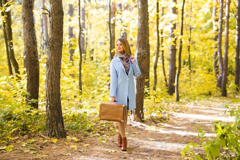 Seizoen, aard en mensenconcept - Vrouw in de herfstpark die zich met koffer bevinden stock foto