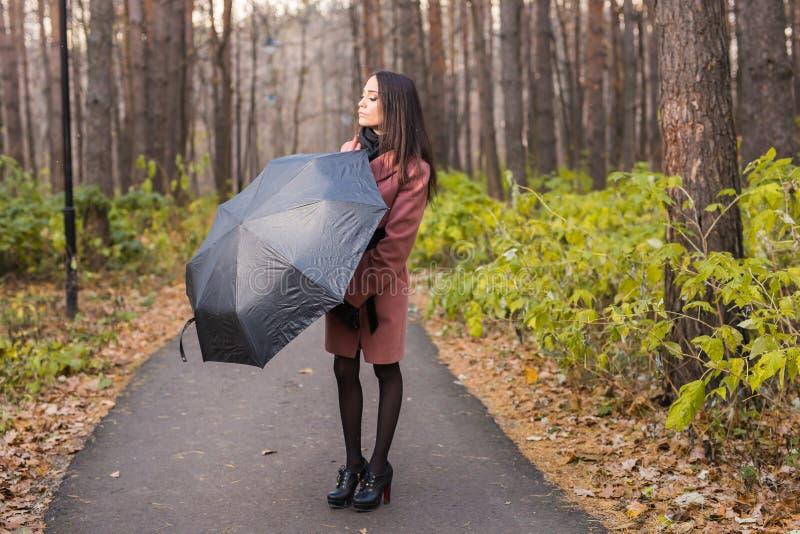 Seizoen, daling en mensenconcept - Portret van mooie glimlachende vrouw in roze laag met zwarte paraplu royalty-vrije stock foto