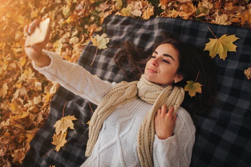 Seizoen, technologie en mensenconcept - mooie jonge vrouw die op grond en de herfstbladeren liggen en selfie nemen met stock fotografie