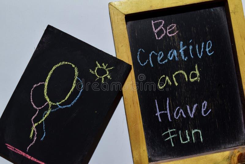 Seja criativo e tenha o divertimento em escrito à mão colorido da frase no quadro-negro foto de stock