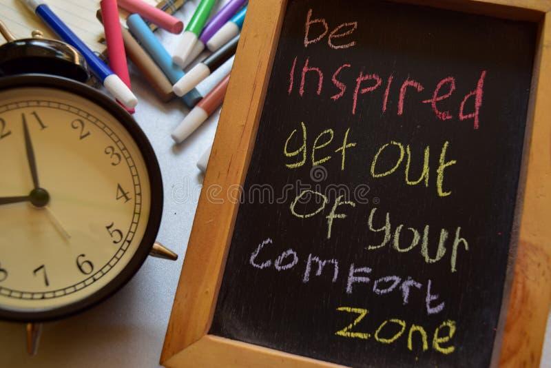 Seja inspirado saem de sua zona de conforto em escrito à mão colorido da frase no quadro, despertador fotografia de stock royalty free