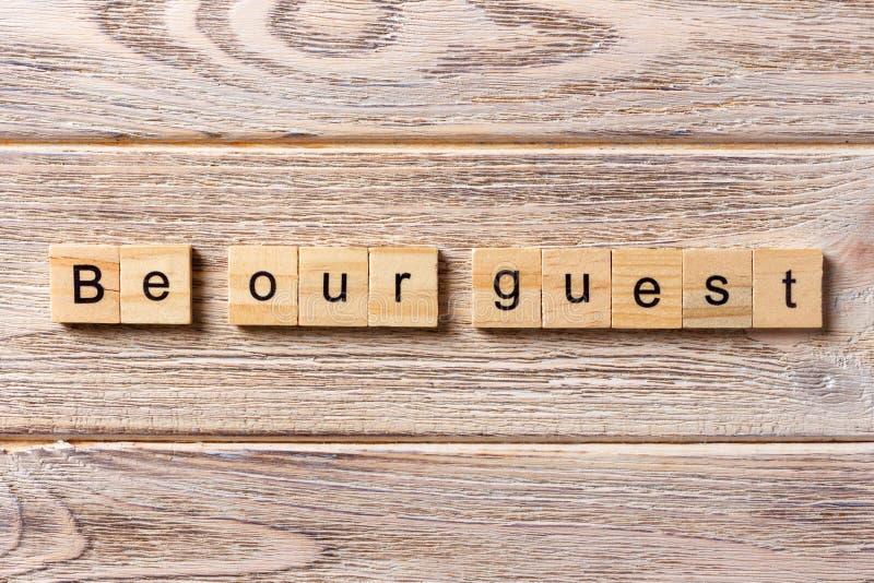 Seja nossa palavra do convidado escrita no bloco de madeira Seja nosso texto na tabela, conceito do convidado imagens de stock royalty free