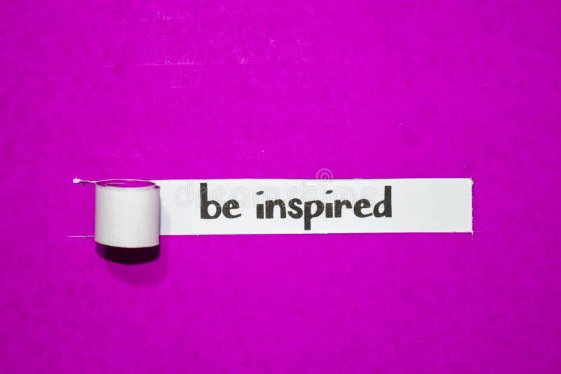 Seja texto inspirado, conceito da inspiração, da motivação e do negócio no papel rasgado roxo fotografia de stock