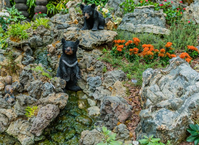 Sejong,, South Korea, August 5, 2019: Ceramic asian black bears posed in artificial landscape of flowers, boulders and mountain. Stream royalty free stock photo