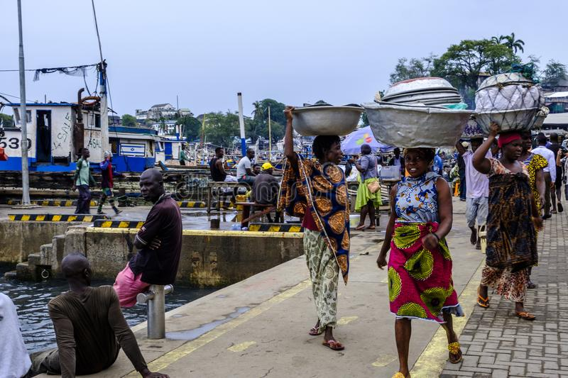 Sekondi fish market women. SEKONDI TAKORADI, GHANA – 10 APRIL 2018: Women in colorful dress carry tin buckets on their heads ready to sell fish at busy royalty free stock photo