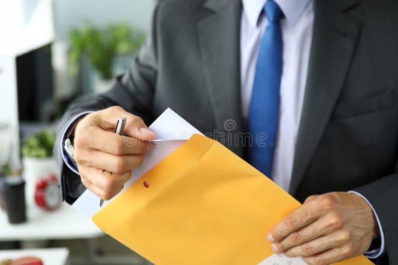Sekretär im Anzug und Bindung am verpackenden Umschlag des Arbeitsplatzes, der Umschlag mit wichtiger Dokumentation auspackt lizenzfreies stockfoto