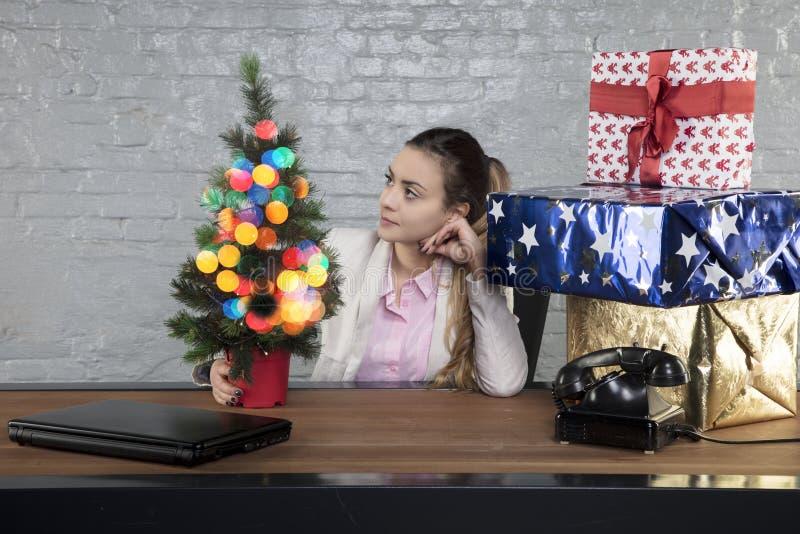 Sekretär starrt entlang des Weihnachtsbaums, lächelndes Gesicht an lizenzfreie stockbilder