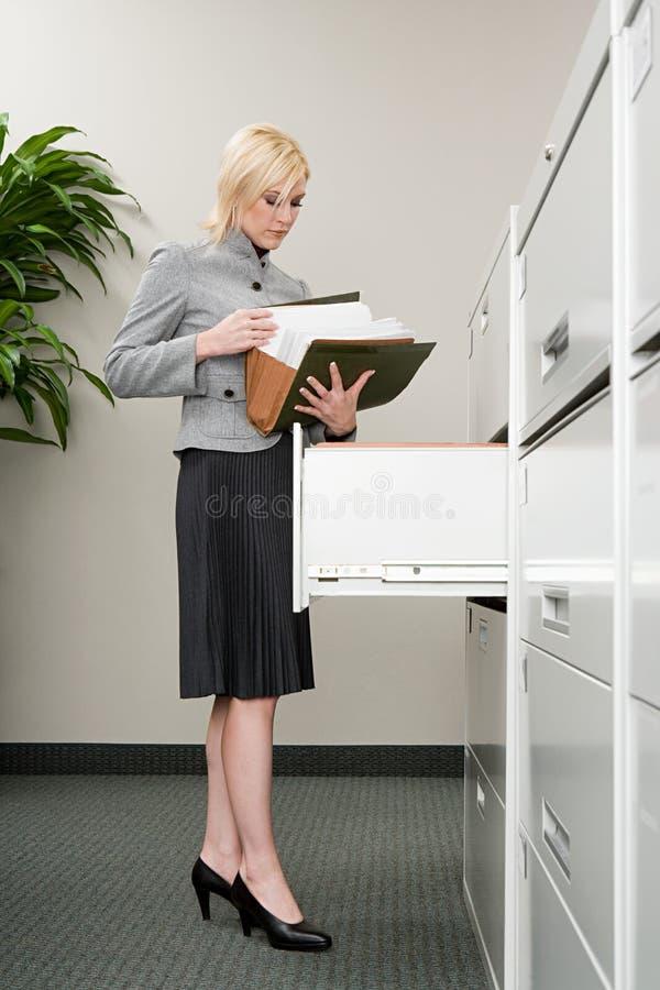 Sekretarka patrzeje kartoteki zdjęcia stock