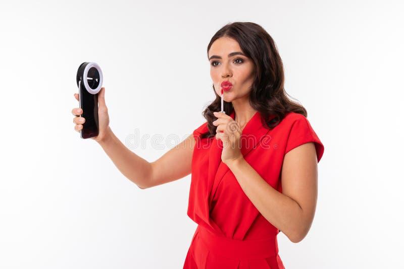 Sekreterare i bakgrunden av en vit vägg rättar till smink, en flicka tittar i en smartphone och målar sina läppar royaltyfria bilder