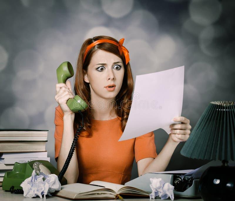 Sekreterare nära skrivmaskins- och visartavlatelefonen royaltyfri fotografi