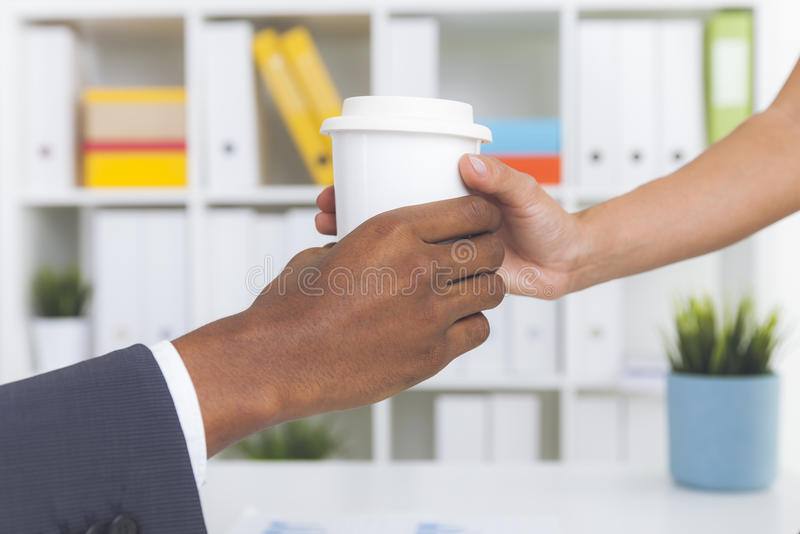 Sekreterare som ger kaffe till hennes framstickande royaltyfri foto