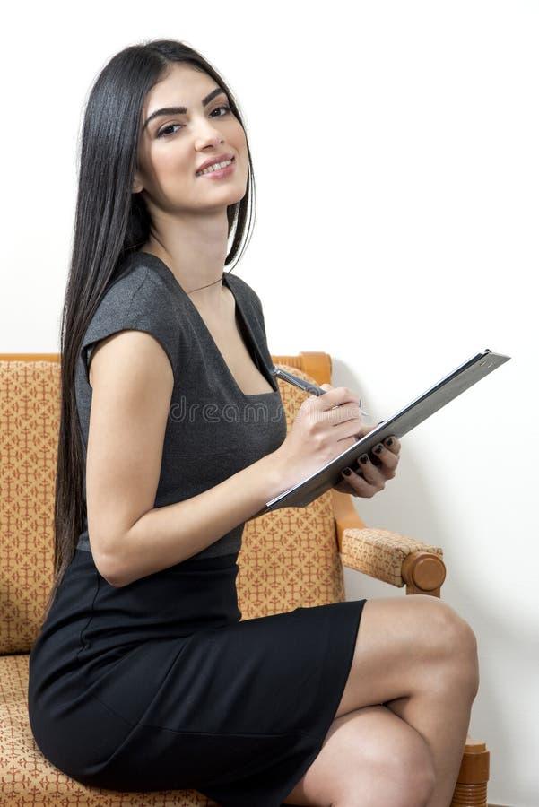 Sekreterare som ler, medan ta anmärkningar arkivbilder