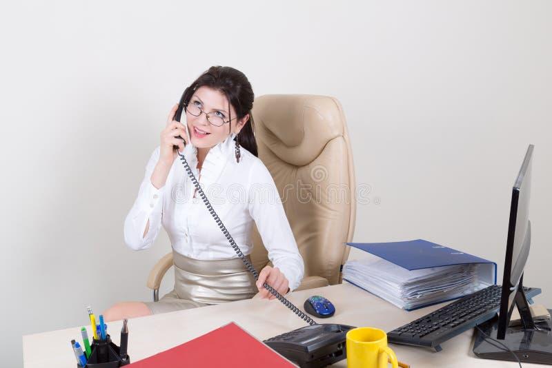 Sekreterare som talar på telefonen arkivfoton