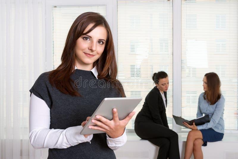 Sekreteraren som ler flickan, läser informationen från minnestavlan arkivfoto