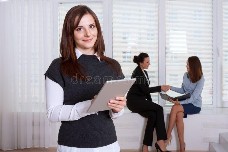 Sekreteraren som ler kvinnan, läser information från minnestavlan royaltyfri fotografi