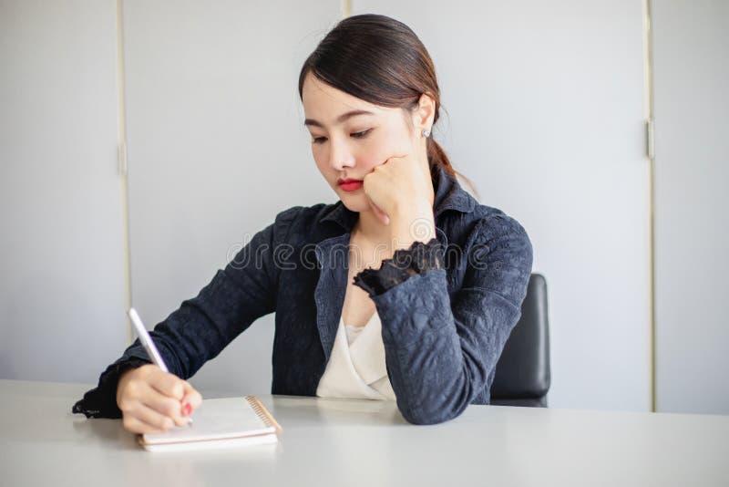 Sekreteraren tar anmärkningar av mötet och arbetar stressfully royaltyfri bild