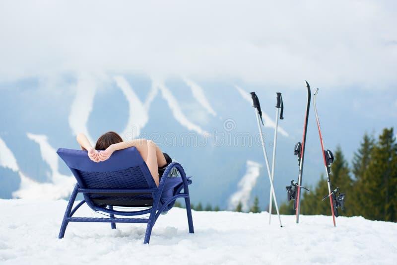 Seksowna żeńska narciarka na błękitnym pokładu krześle blisko nart przy ośrodkiem narciarskim fotografia stock