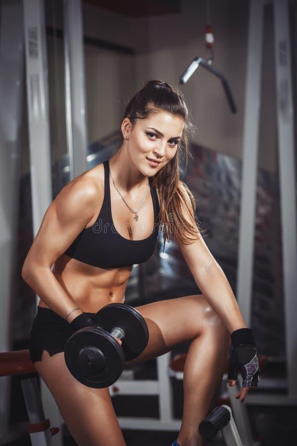 Seksowna atlety dziewczyna ćwiczy z dumbbells w gym obraz royalty free