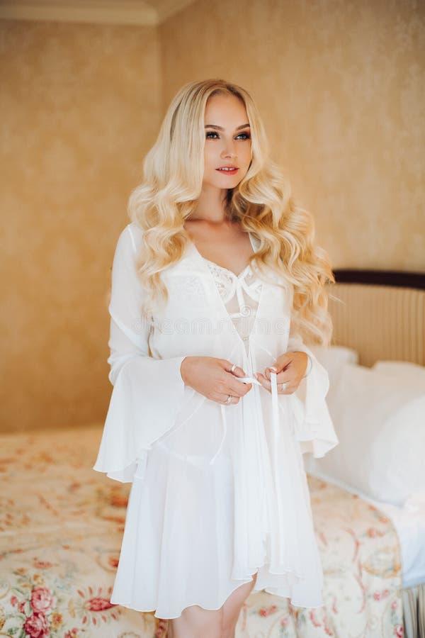 Seksowna blondie panna młoda w biel koronki bielizny rozbierać się zdjęcia stock