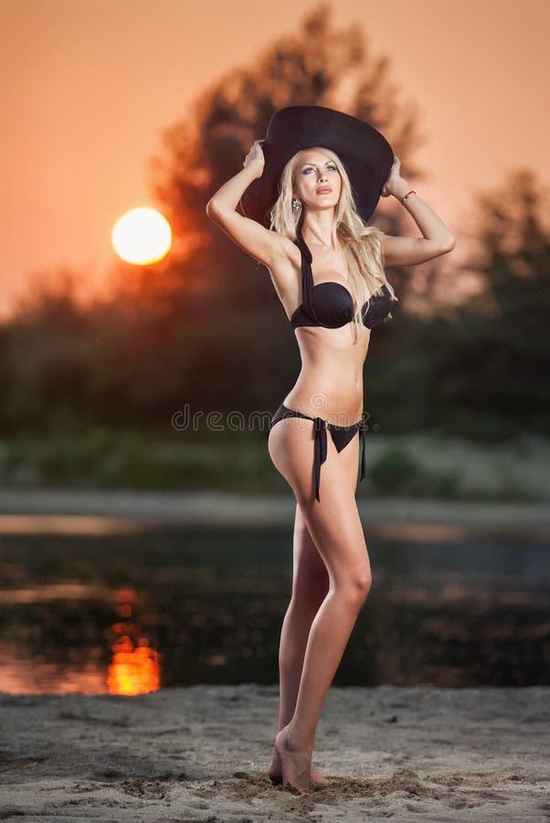 Seksowna blondynki dziewczyna w czarnym bikini przy plażą zdjęcie royalty free