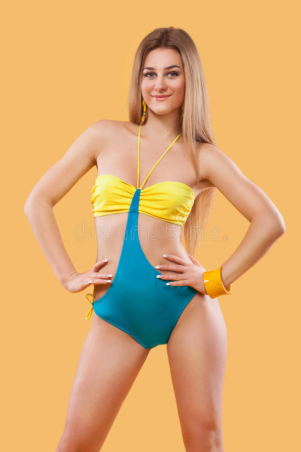 Seksowna blondynki kobieta jest ubranym różowego swimwear pozuje na koloru tle idealne ciało Bikini katalog zdjęcia royalty free