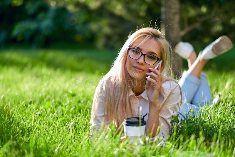 Seksowna blondynki kobieta opowiada na lying on the beach na łące i telefonie komórkowym obraz stock